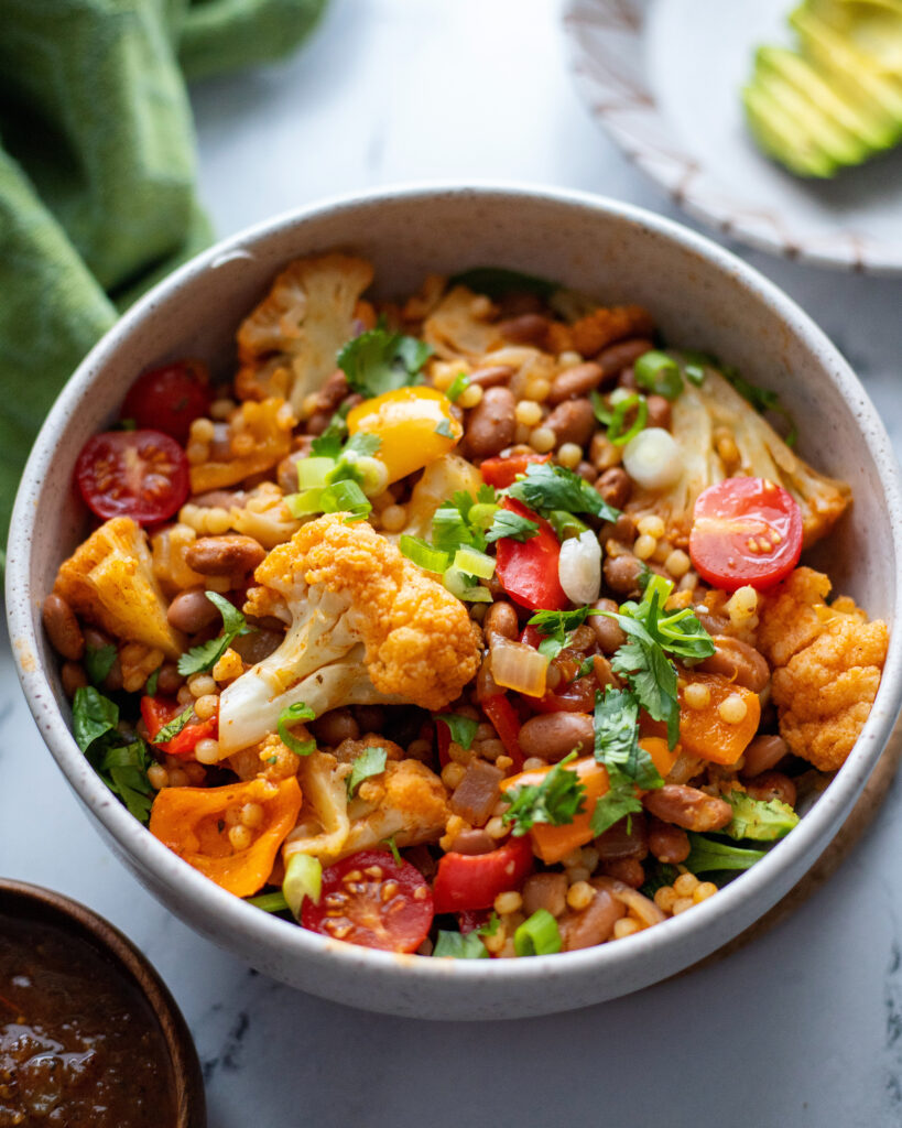 Creole Spiced Pinto bean and pearl cous cous bowl with vegetables